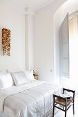 Light-flooded bedroom with stucco ceiling and arched window