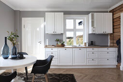 Modern, white, country-house kitchen with dining area and grey walls