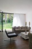 Simple living room with open terrace doors leading into garden