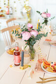 Table set with waffles and lemonade decorated with peonies