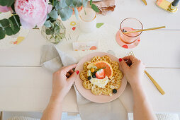 Waffle with fruit and cream on festively set table