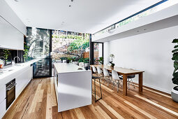 Large, modern kitchen with long dining table and access to garden