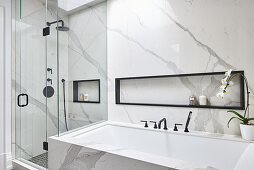 Marble bathroom with bathtub and glass shower