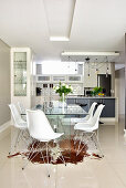 Glass table, classic chairs, cowhide rug and shiny tiled floor in elegant dining area