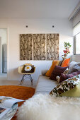 Scatter cushions on sofa and classic chair below triptych artwork in modern interior