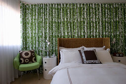 Double bed with rattan headboard, bedside cabinets and green armchair against green-and-white curtain in bedroom