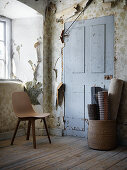 Wooden chair and rolled rugs in room with peeling wallpaper
