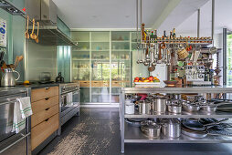 Island counter with stainless steel shelves below in open-plan kitchen
