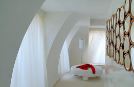 Round, white ottoman in elegant room with partition wall