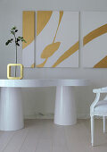 White table with organic shape, single rose in vase and triptych artwork