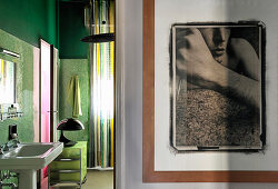 Large photo on wall and view into bathroom with green mosaic tiles