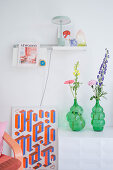 Vases of flowers, picture leaning against wall and ornaments on shelf providing accents of colour