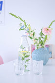 Flowers in pale blue vase, bottle of water and drinking glasses on dining table