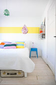 White bedroom with various accents of bright colour