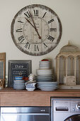 Stacked crockery and bird cage on kitchen counter below large clock on wall