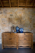 Blue-and-whit vases and lantern on rustic wooden cabinet against stone wall