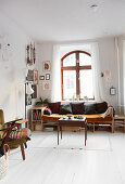Sofa with storage compartments in front of arched window in window bay