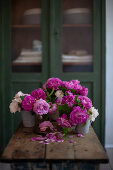 Pink and white roses in metal vases on wooden table
