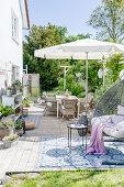 Sommerterrasse mit Hängesessel und Sonnenschirm