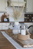 Summery arrangement of lantern and blue-and-white ceramic vase on driftwood board on kitchen table