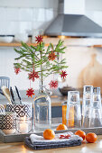 Fir branch with decorations in swing-top bottle. glasses and cutlery on tray behind tangerines on folded tea towels