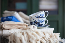 Folded tablecloths and blue-and-white cups