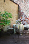 Round table and folding chairs on terrace in idyllic courtyard