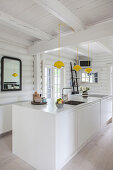 White island counter in kitchen of in white-painted log cabin