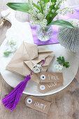 Gebastelte Osterdeko in Naturtönen und Violett auf einem Schneidebrett