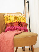 Multicoloured cushion made from knitted tubes made using knitting dolly