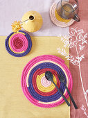 Handmade coasters and mat made from knitted tubes made using knitting dolly