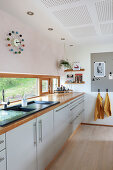 Pale kitchen counter below ribbon window
