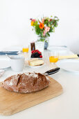 Bread with knife on wooden board on set table