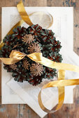 Christmas arrangement of pine cones and gold ribbon