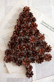 Christmas-tree shape made from pine cones on book pages