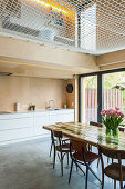 Dining table in open-plan kitchen with net instead of solid ceiling