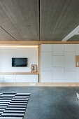 Fitted cupboards with white fronts in open-plan interior with concrete elements