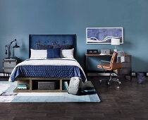 Double bed with blue headboard, next to desk with leather chair against blue wall