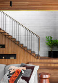 Sofa with pillows, stairs in the background, wall of stairs with wooden paneling