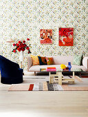 Upholstered sofa, side table with bouquet of roses, armchair and coffee table in the living room with floral wallpaper, pictures on the wall
