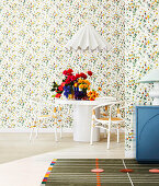 White dining table with flowers and chairs in front of floral wallpaper, white designer hanging lamp