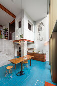 Open-plan, double-height interior with bright blue floor tiles and concrete and brick walls