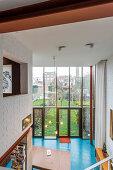 Open-plan, industrial-style interior floor-to-ceiling glass wall overlooking garden