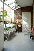 Summery loggia with glass roof, brick wall and white floor