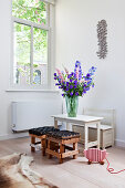Vase of delphiniums on child's table with bench and stools