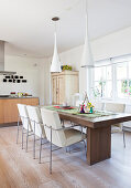 Chairs with white upholstery around dark dining table in modern kitchen-dining room