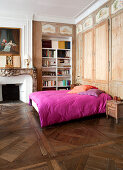 Old parquet floor and fitted wardrobes in bedroom with hot-pink bed linen on double bed