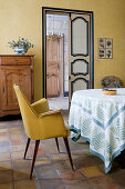 Yellow armchair next to table in Mediterranean dining room with terracotta floor tiles