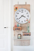 Clock and small vases mounted on wooden board on wall