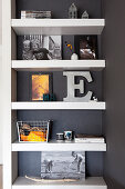 Decorative letters and photos of children on floating shelves on dark wall